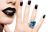 Macro shot of a woman's lips and nails painted bright color blac — Stock Photo