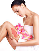 Beautiful young woman with flowers using a scrub. — Stockfoto