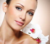 Face of  beautiful woman with a white orchid flower — Stock Photo