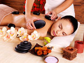 Adult woman having hot stone massage in spa salon — Stock Photo