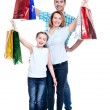 Happy american family with child holding shopping bags — Stock Photo #43174955