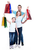 Happy american family with child holding shopping bags  — Stock Photo