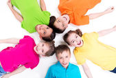 Five smiling children lying on the floor. — Стоковое фото
