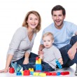 Smiling young family playing with a baby. — Stock Photo