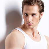 Handsome man in white shirt poses at studio. — Stock Photo