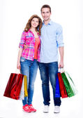 Happy couple with colored shopping bags. — Stock Photo