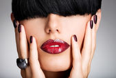 Closeup face of a woman with beautiful sexy red lips and dark na — Stock Photo