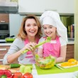 Happy mother and daughter cooking a salad. — Stock Photo #47297661