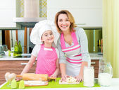 Happy mother and daughter making pies. — Stock Photo