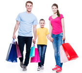 Family with shopping bags standing at studio. — Stock Photo
