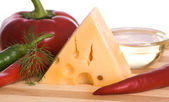 Cheese and pepper on wooden board — Stock Photo