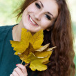 Woman holding a yellow autumn leaves — Stock Photo
