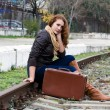 Beautiful girl sitting on a suitcase along the train tracks — Stock Photo
