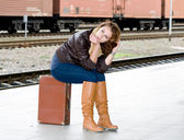 Girl is sitting on a suitcase waiting for the train — Stock Photo
