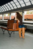 Girl with vintage suitcase sits on the ramp — Stock Photo