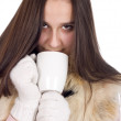 Stock Photo: Womin winter clothes and white gloves, drinking teand warme