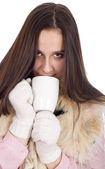 Woman in winter clothes and white gloves, drinking tea and warme — Stock Photo