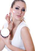 Beautiful woman applying moisturizer cream — Stock Photo