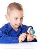 Boy attentively examines the globe — Stock Photo