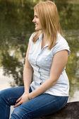 Jeune femme assise sur un lac — Photo