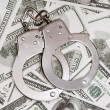 Dollars and handcuffs - Stock Photo