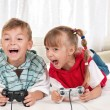 Happy girl and boy playing video game — Stock Photo #13735294