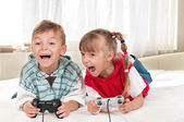 Happy girl and boy playing a video game — Stock Photo