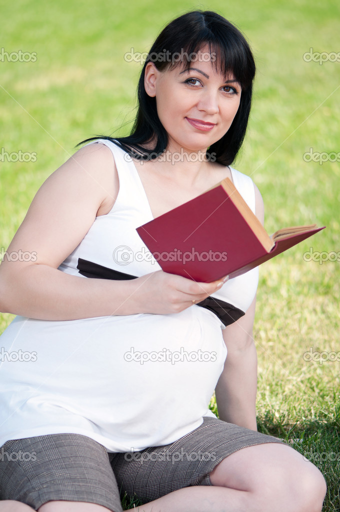 Happy pregnant woman with book in park outdoors — Stock Photo #15410515