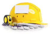 Yellow hard hat with work gloves and tools — Stok fotoğraf