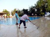 Alania, Turkey - August 31, 2008: Cleaner wash the floor near swimingpool on August 31, 2008 in Alania, Turkey — Stock Photo