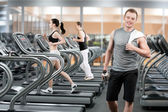 Young man in fitness club — Stock Photo