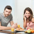 Couple having breakfast, girl talking on the phone — Stock Photo