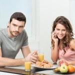 Couple having breakfast, girl talking on the phone — Stock Photo #27052467