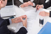 Hands of three people, signing documents — Stock Photo