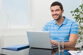 Happy businesswoman sitting at table with laptop — Stock Photo