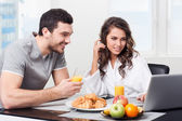 Beautiful couple having breakfast with a laptop — Stock Photo