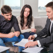 Agent advises the couple, signing documents — Stock Photo #30041441