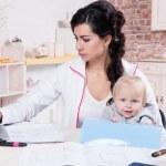 妇女抱着婴儿在家工作 — 图库照片