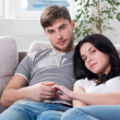 Young couple are sitting down on a couch — Stock Photo