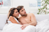 Young couple lying in bed watching television — Stock Photo