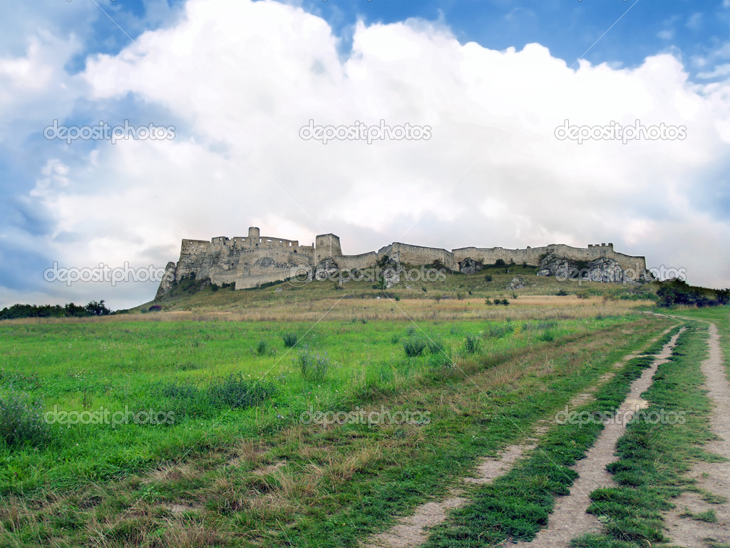 View of field road to famous Spis Castle (Spissky hrad) ruin in summer. This castle is included in the UNESCO World Heritage List. Spis Castle is one of the biggest European castles by area (41 426 m) and is definitely worth a visit.  Stock Photo #13192337