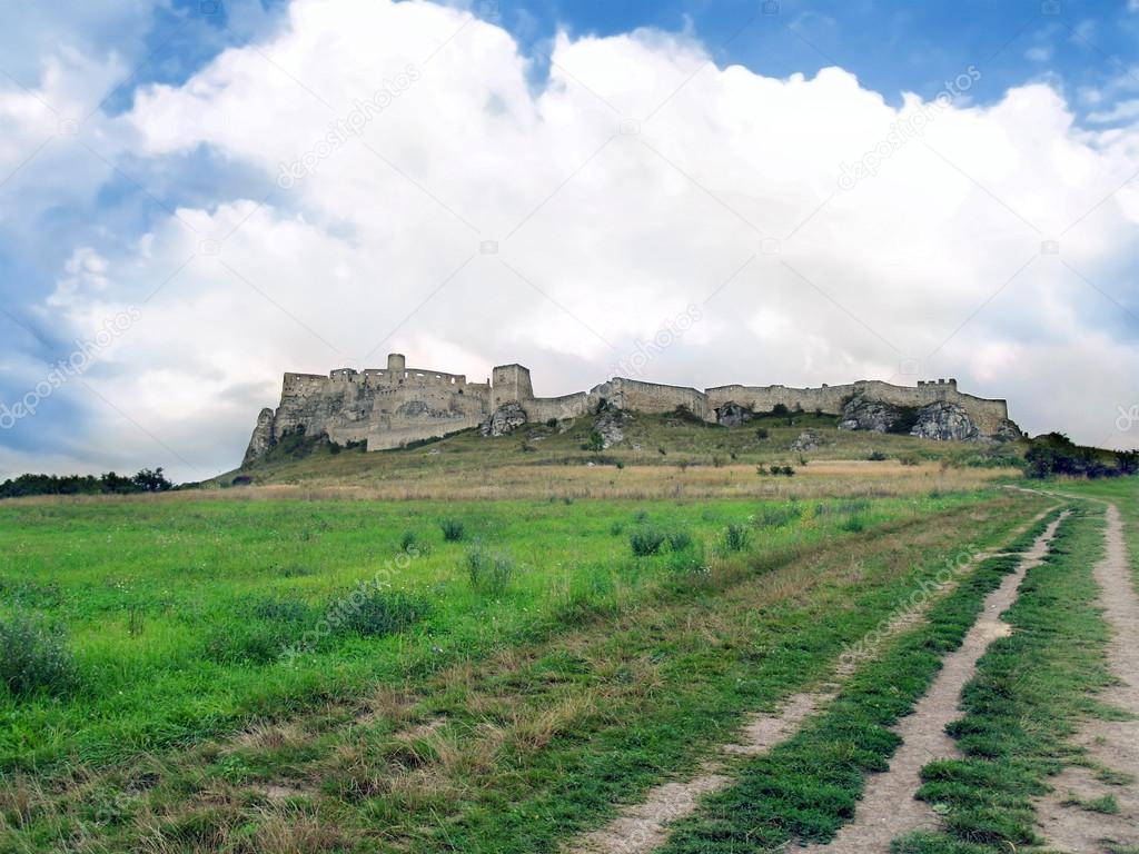 View of field road to famous Spis Castle (Spissky hrad) ruin in summer. This castle is included in the UNESCO World Heritage List. Spis Castle is one of the biggest European castles by area (41 426 m) and is definitely worth a visit.  Foto Stock #13192337