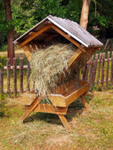 Sheltered wooden feeder fully filled with hay — Zdjęcie stockowe