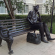 Student with laptop sits on the bench, statue, Kharkov, Ukraine — Stock Photo
