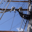 Crew unfurls a sail on a yardarm of a tallship — Stock Photo