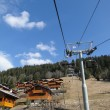 Alpine chalets under ski lifts — Stock Photo
