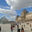 Tourists gather in courtyard of Louvre Museum — Stock Photo #12863408