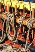Coiled rope lines stored on belaying pins — Stock Photo