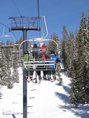 Skiers ride the chairlift through a spruce forest — Stock Photo
