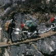 Sherpa and yak crossing suspension bridge - Stock Photo